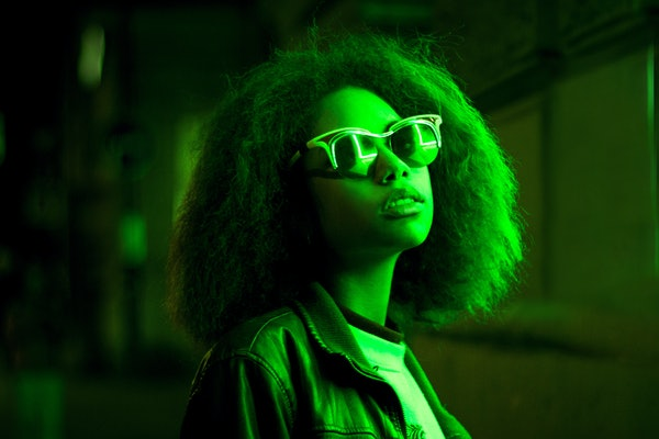 High Fashion. Young Beautiful woman with Trendy glowing neon hairstyle, stylish makeup. Sexy adorable night Party Model Girl in green street neon light. Creative Colorful fashionable Portrait