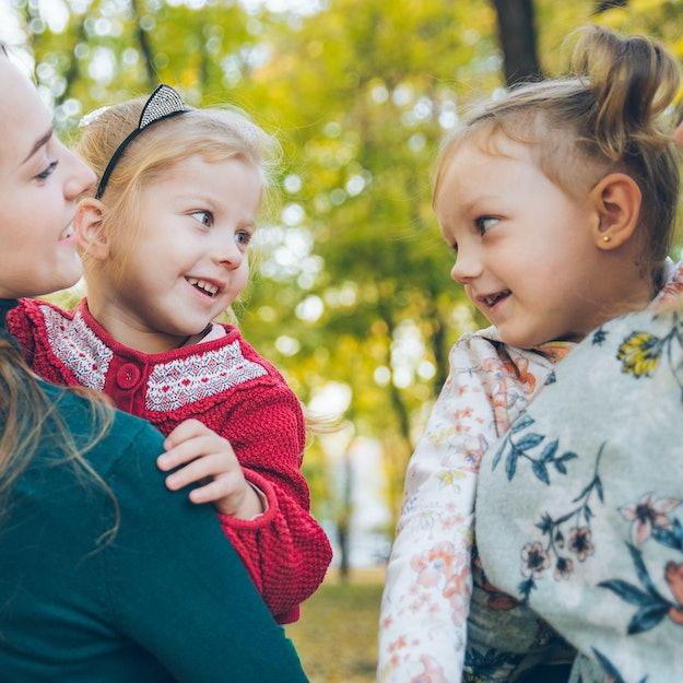 mother daughter love hug at autumn city park fall season