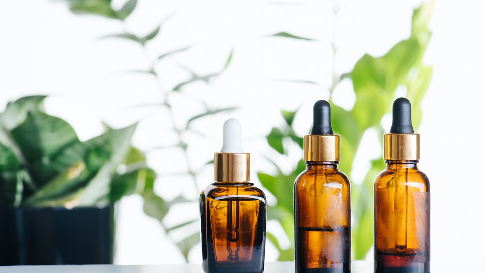 Transparent cosmetic amber glass dropper bottles over green plants on white background. Vials with pipette plastic caps for essential oils, perfumes and skincare substances. Three in a row.