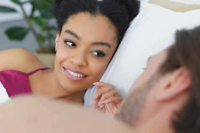 partial view of young interracial couple lying in bed in morning at home