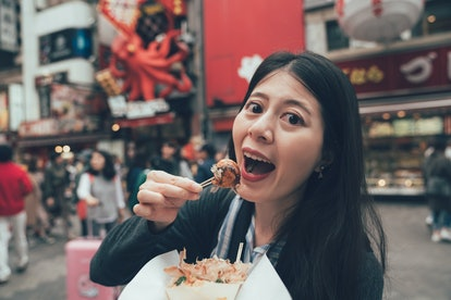 korean female model tourist eating octopus ball dumpling showing face camera open wide mouth. happy ...