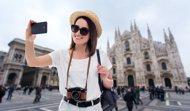 portrait of young beautiful woman tourist taking selfie photo with smartphone in Milan, Italy