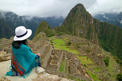 Female Traveler Sitting on the Cliff Looking at the Inca ruins of Machu Picchu, UNESCO World Heritag...