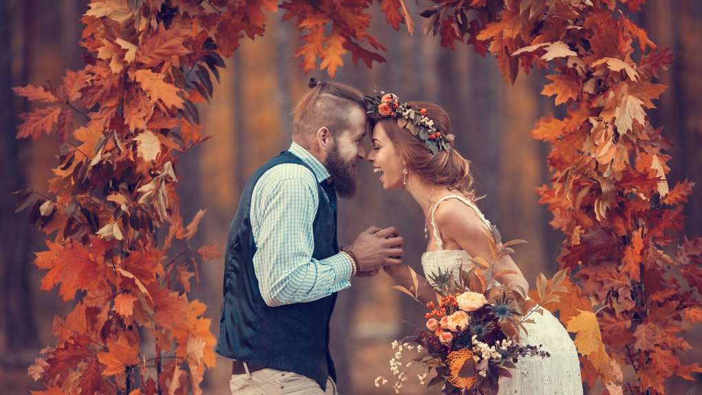 Beautiful bridal couple, bearded bride and groom in a wreath, laughing happily in the arch of autumn oak leaves