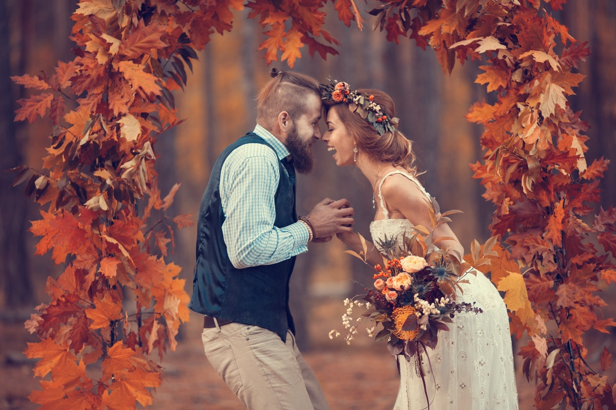 Beautiful bridal couple, bearded bride and groom in a wreath, laughing happily in the arch of autumn...
