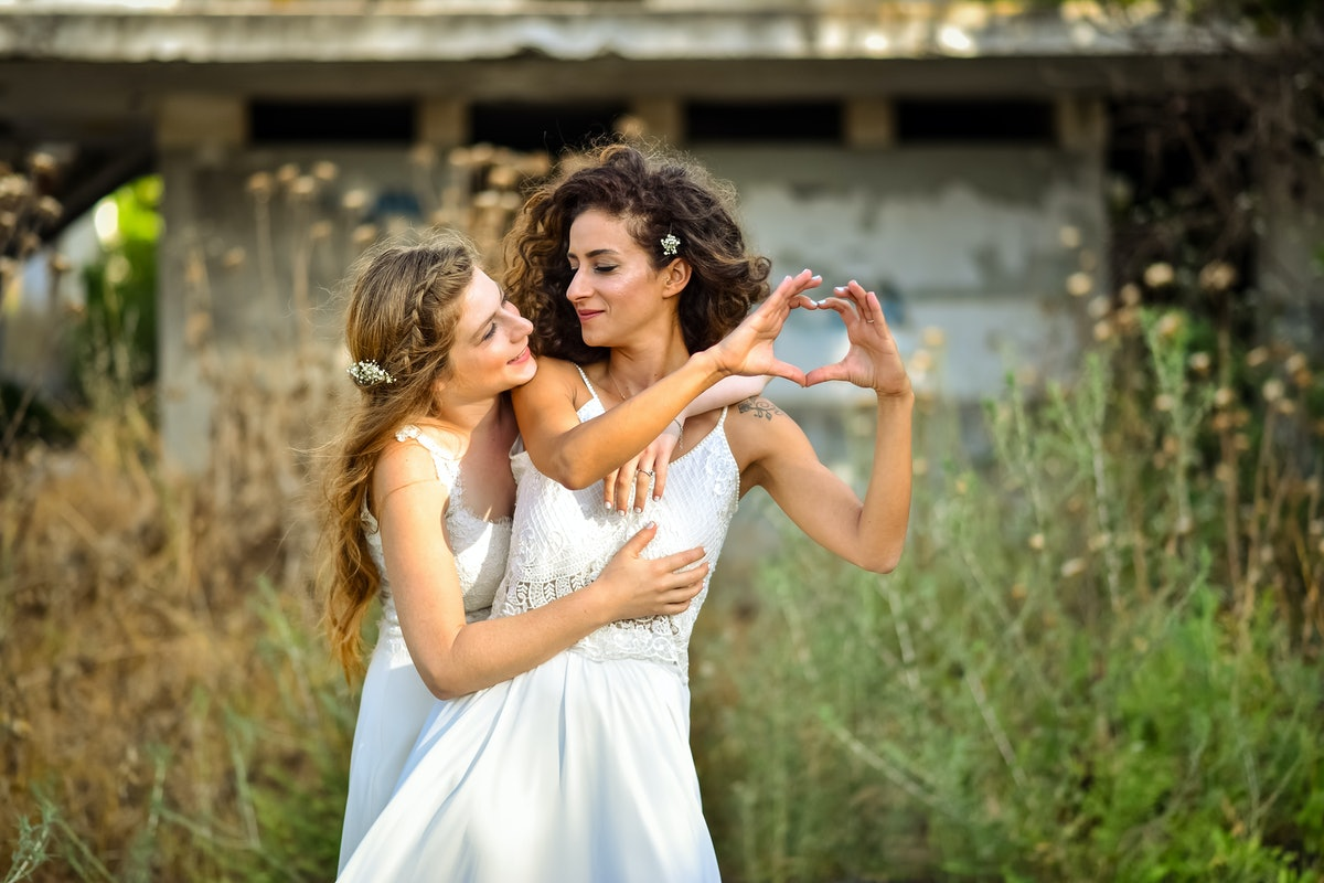 two brides white dresses, one creates a heart shape using the fingers of the hands. the other one lo...