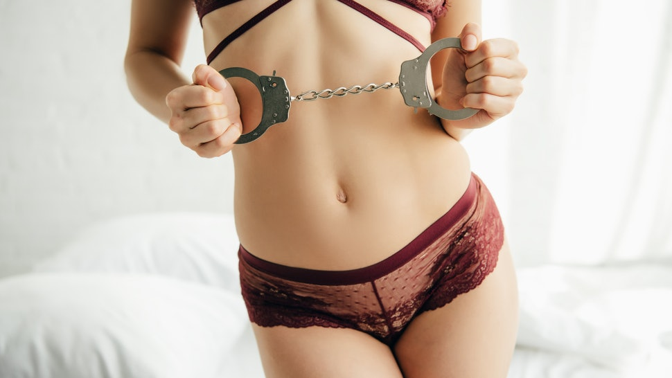 cropped view of sexy woman holding handcuffs while standing in lingerie