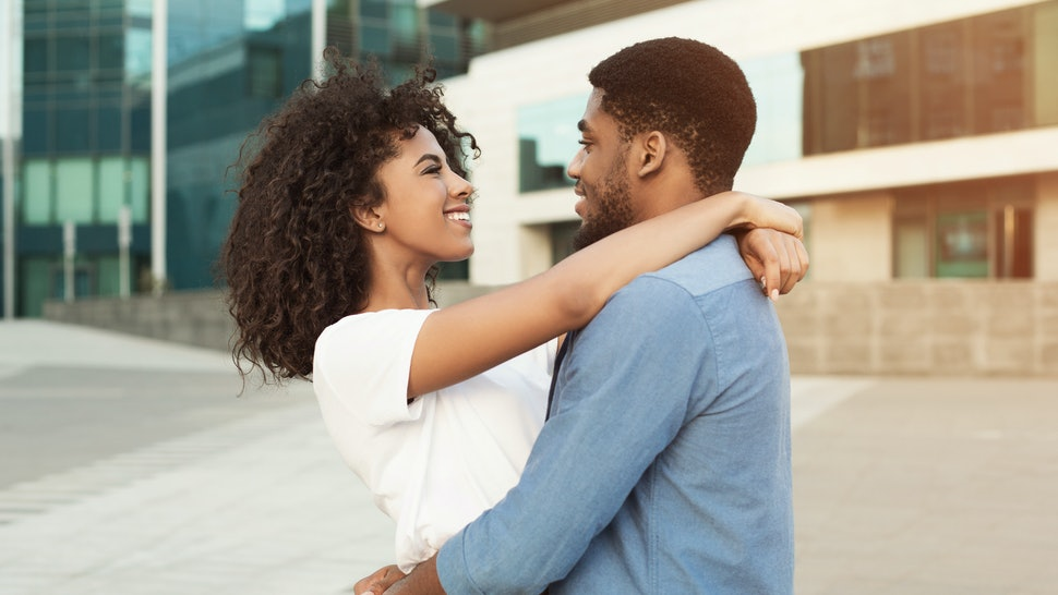 Couple date. Romantic african-american pair hugging and walking in city