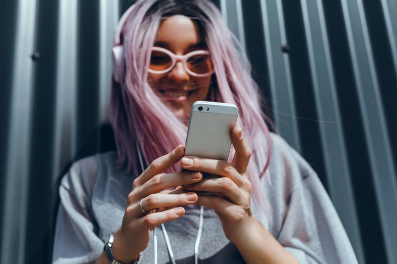 A happy girl with pink hair and headphones looks at her phone.