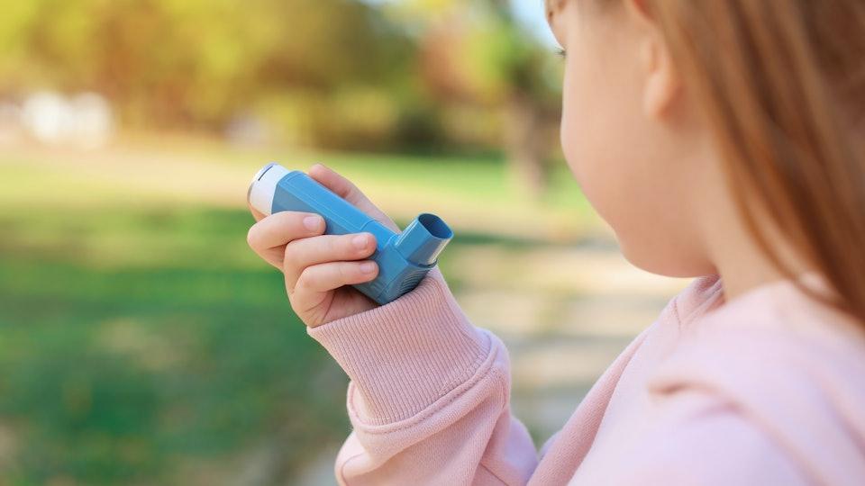 Little girl using asthma inhaler outdoors. Health care