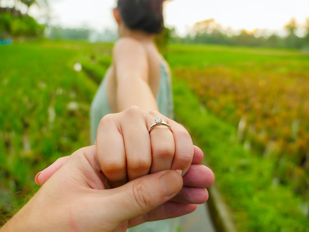 close up couple hands man holding happy fiance hand with diamond engagement ring on her finger after...