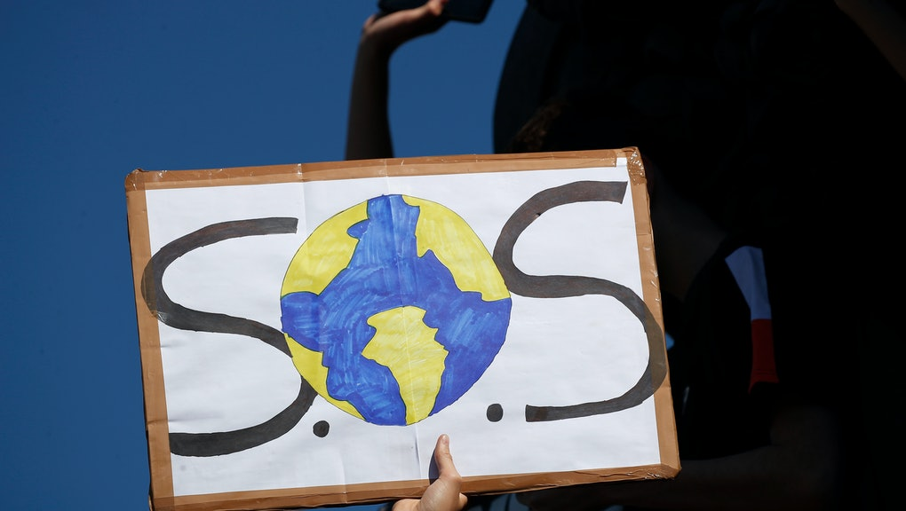 A protester shows a placard during a climate demonstration in Paris. In Canberra and Kabul, Cape Tow...