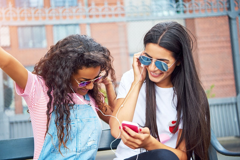 Two smiling young girlfriends singing while sitting on a city bench in the summer listening to music together on a shared pair of headphones