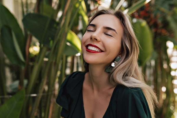 Happy smiling woman with white teeth and red lips feeling happiness while walking outside on the island