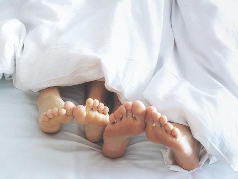 Feet of couple lying on bed under blanket. Morning awaking