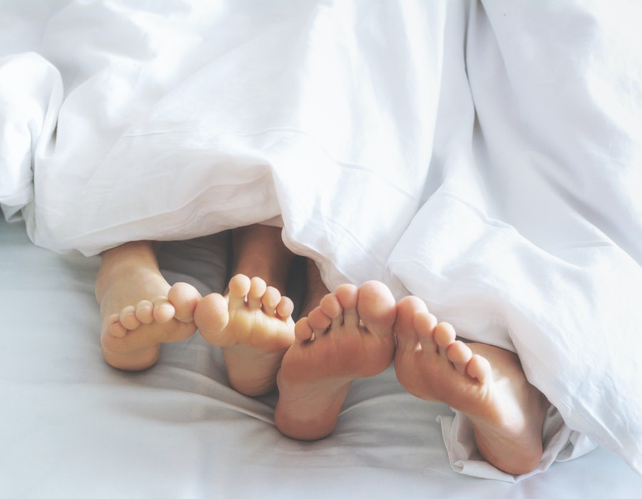 Feet of couple lying on bed under blanket. Morning awaking