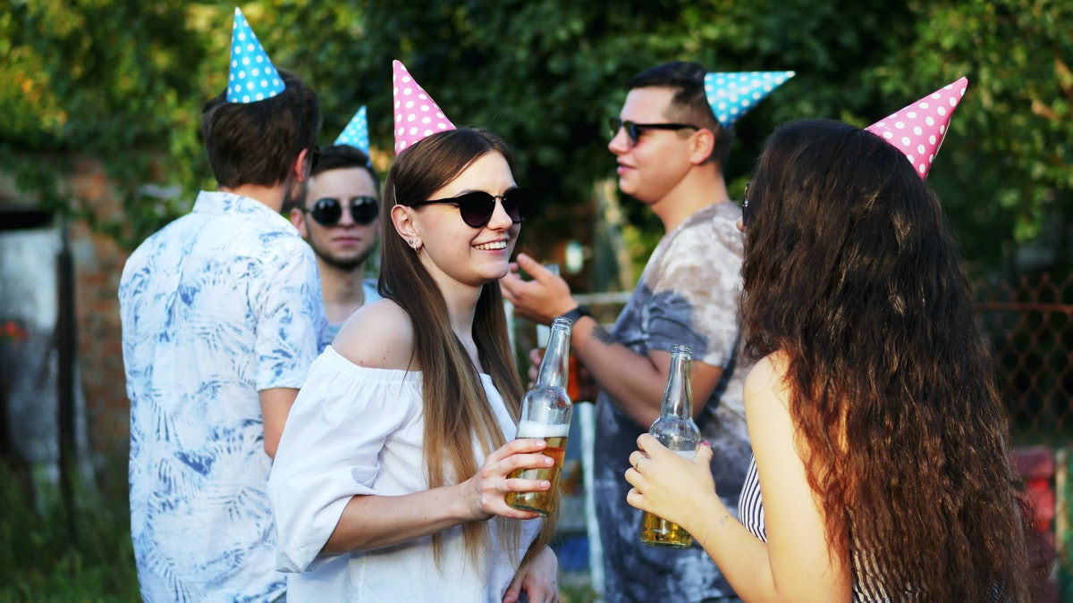 Two happy woman talking and drinking beer from bottle on summer party, men in the background, wearin...