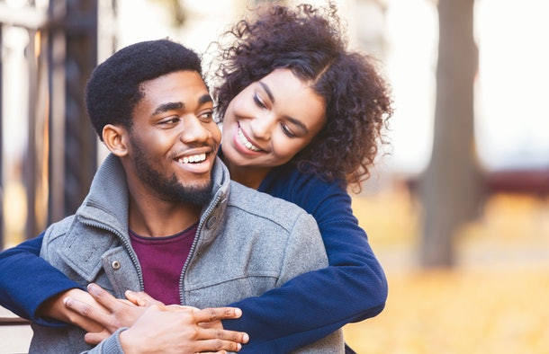 Do you love me. Attractive black girl flirting with her handsome boyfriend, spending time together at autumn city park, empty space