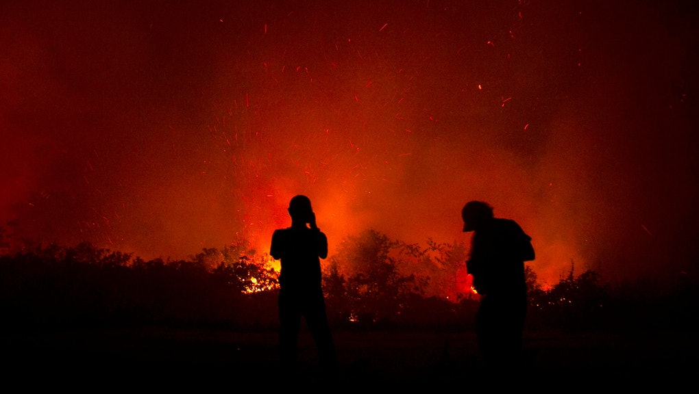 Residents inspect a fire in Palangkaraya, Central Kalimantan, Indonesia, 23 September 2019 (issued 24 September 2019). Firefighters, military personnel and water-dropping helicopters have been deployed to combat the fires in Sumatra and Borneo that have caused thick haze in the neighboring countries, Singapore and Malaysia.