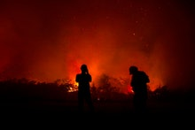 Residents inspect a fire in Palangkaraya, Central Kalimantan, Indonesia, 23 September 2019 (issued 2...