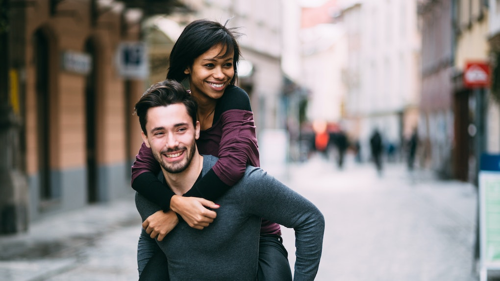 Young man giving girlfriend piggyback ride