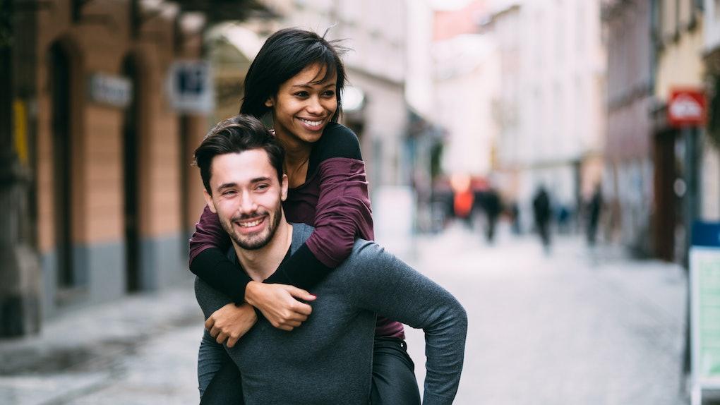 Young man giving girlfriend piggyback ride