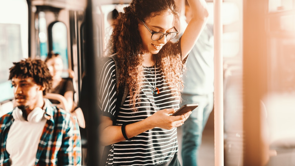 Beautiful mixed race girl with long curly hair using smart phone for reading or writing message while standing in city bus.