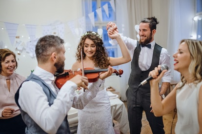 A young bride, groom and other guests dancing and singing on a wedding reception.