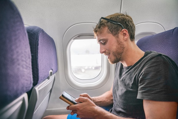 Plane passenger man texting on mobile phone using in-flight onboard wifi internet on business travel trip holding cellphone. 5G technology device.