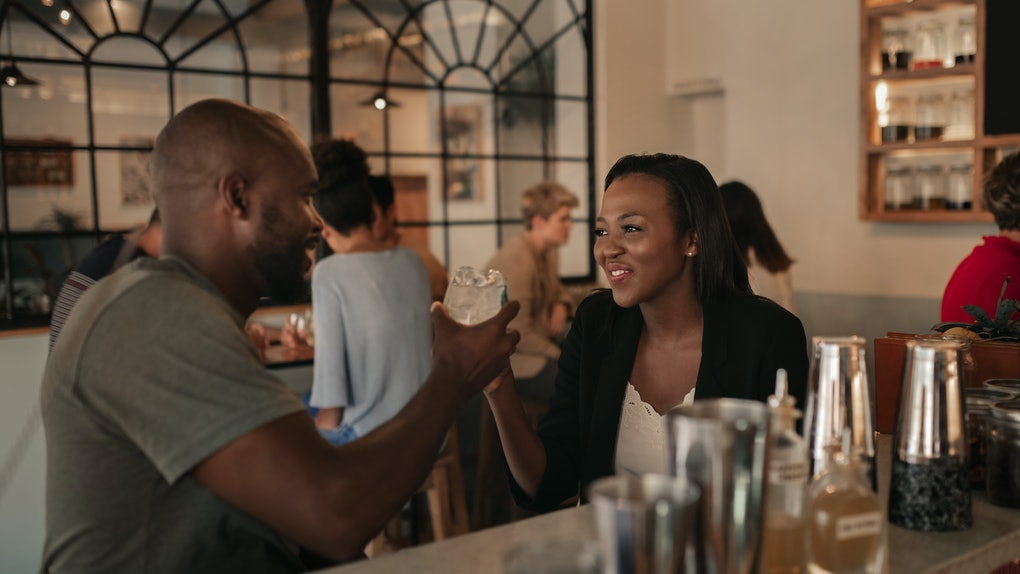 Smiling young African American couple sitting at the counter of a bar toasting with drinks while on a date together