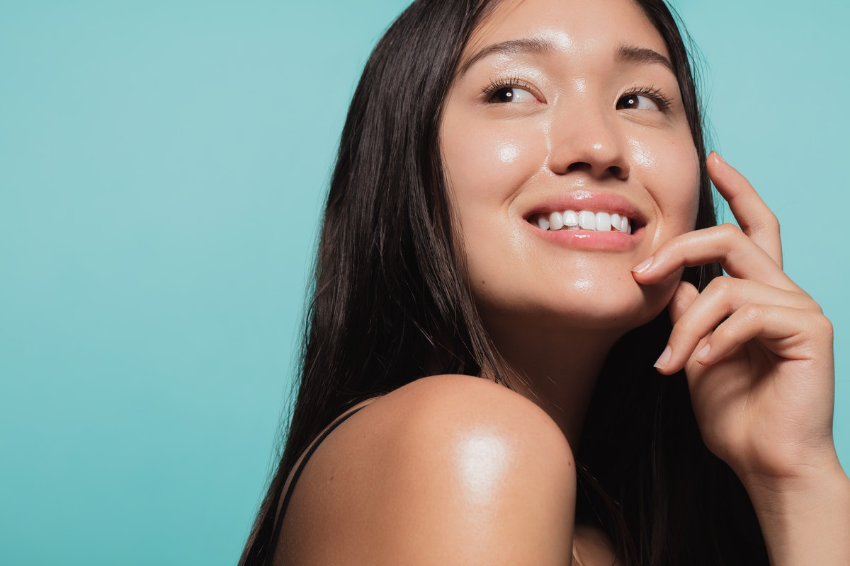 Close up of cute asian girl with glowing skin against blue background. Beautiful face of girl with f...