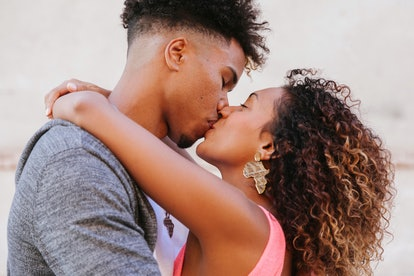 close up of heterosexual ethnic couple kissing outdoors
