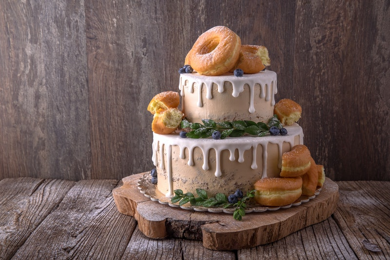 Wedding cake decorated with donuts and wild berries. Fashionable luxury stylish cake