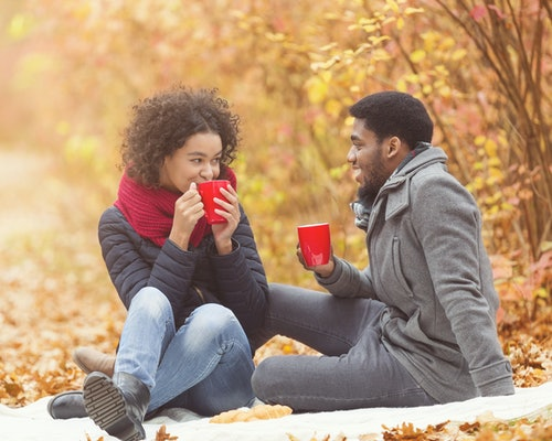 Cozy fall. Afro couple drinking hot coffee, having picnic in forest, sitting on plaid