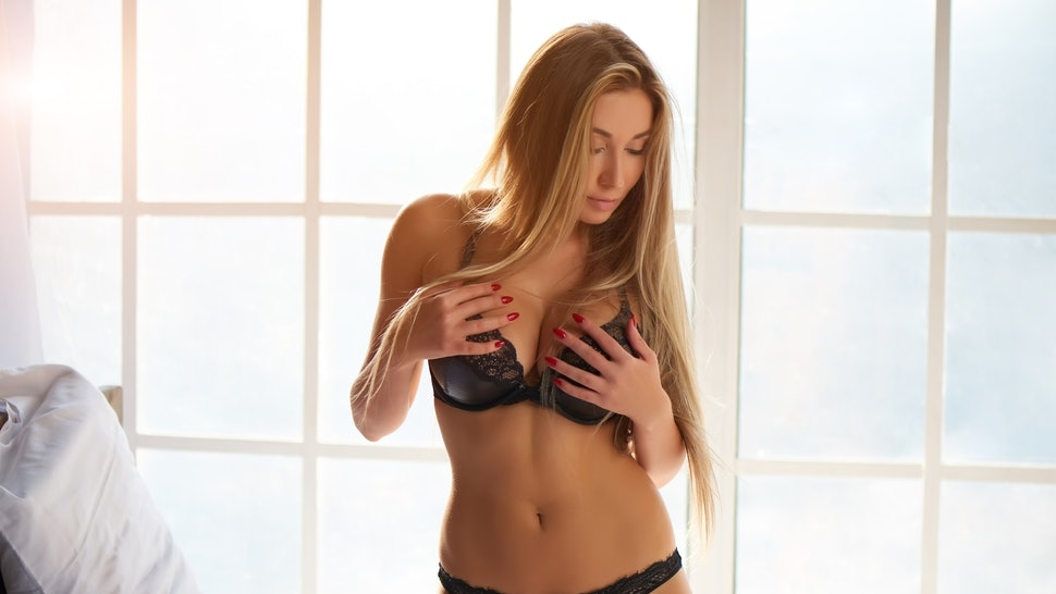 Attractive caucasian girl, black underwear. Sexy woman in bedroom.