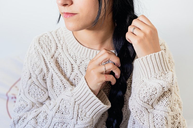 Close up of a beautiful young woman smiling and doing a braid in her hair in winter outfit at home