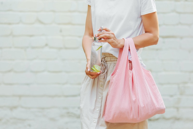 Female hands hold eco bag   and reusable water bottle. Zero waste. Sustainable lifestyle concept.