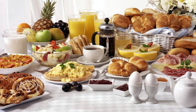 BREAKFAST BUFFET TABLE FILLED WITH ASSORTED FOODS,SAVOURY,SWEET,PASTRIES,HOT AND COLD DRINKS