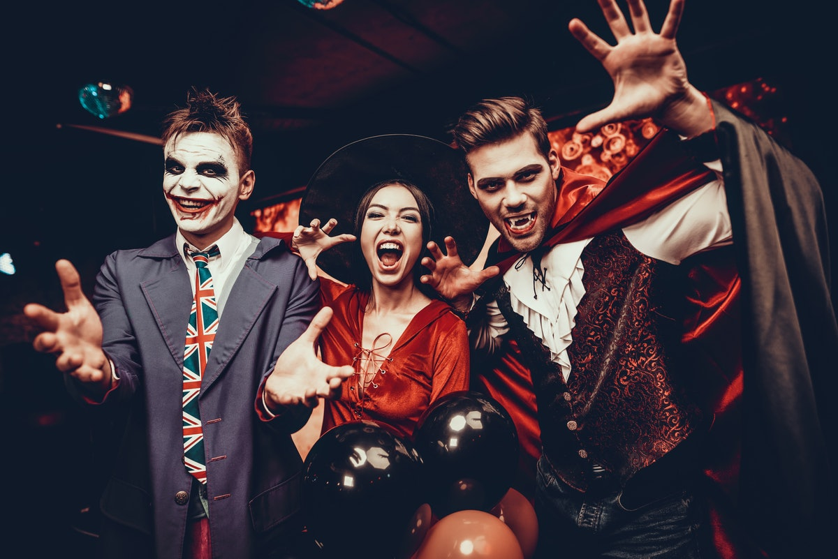Young People in Costumes Celebrating Halloween. Group of Young Happy Friends Wearing Halloween Costu...