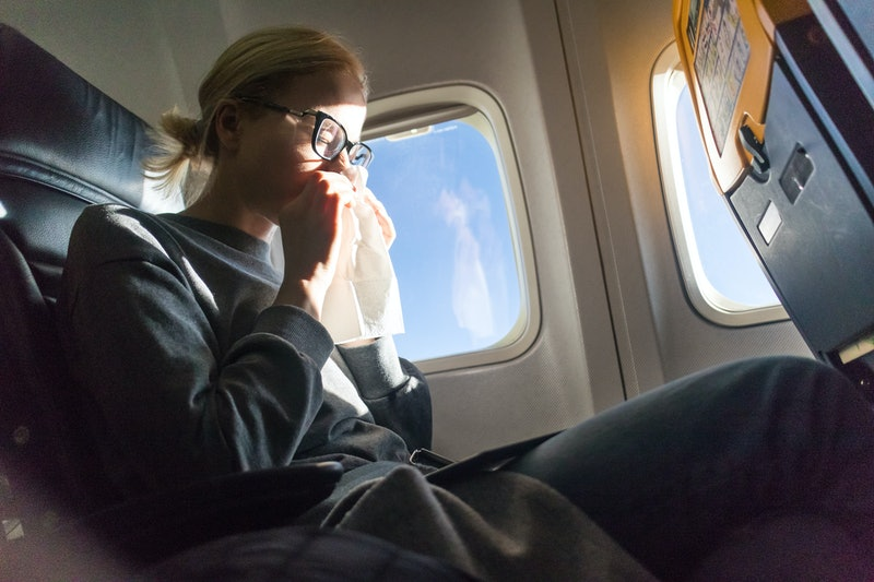 Blonde caucasian woman sneezing while flying by commercila airplane.