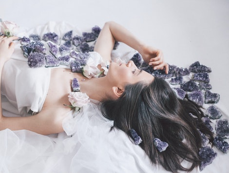 the girl lies in flowers and amethysts