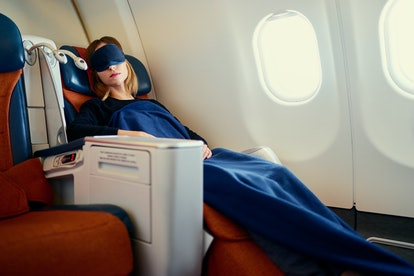 Traveling at first class. Flight with comfort. Pretty young  woman sleeping in airplane.