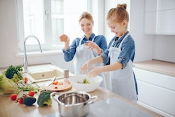 A young and beautiful mother in a blue shirt and apron is preparing a fresh vegetable salad at home in the kitchen, along with her little cute daughters with light hair
