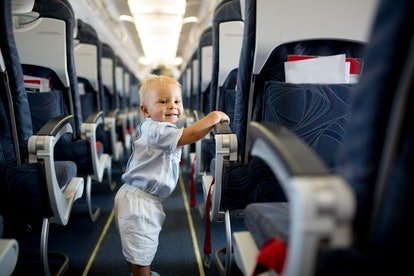 Little baby boy, playing with toys on board of the aircraft, happy traveler