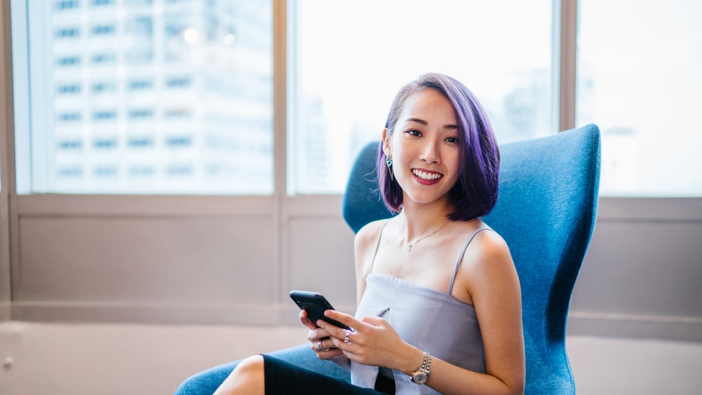 Business portrait of a young, slim, elegant and beautiful Asian business woman sitting in a blue armchair in her office during the day. She is smiling as she looks up from her smartphone.