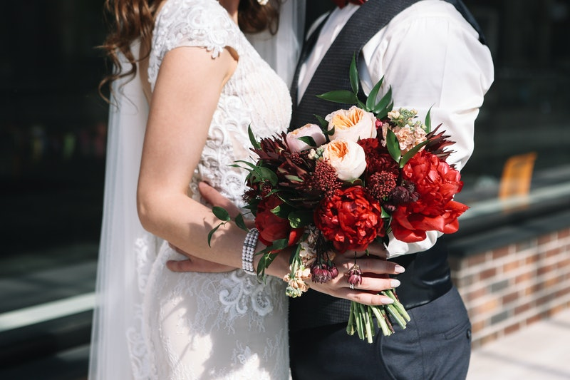 Wedding couple is holding wedding bouquet with peonies, roses and red flowers and greenery in her hand