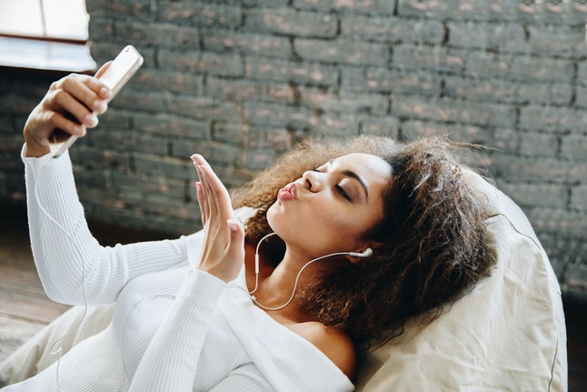 Happy modern African American young girl talking on video chat and lying at home with loft interior, communication concept. Smiling hipster girl making self portrait on her telephone at home