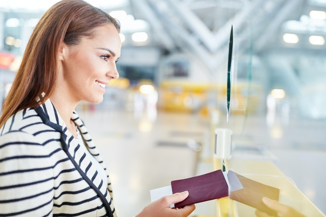 Smiling woman giving me passport at check in desk in airport terminal before departure