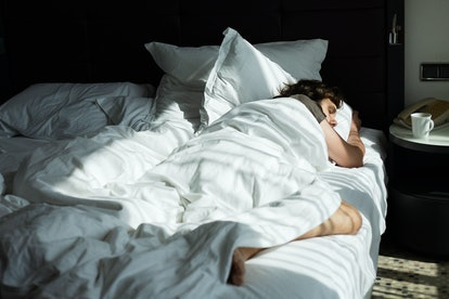 Blond young man is sleeping in a white bed