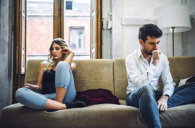 Couple sitting on sofa apart and being angry after quarrel.